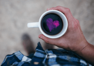 a hand holding a cup of coffee with a purple heart drawn in it