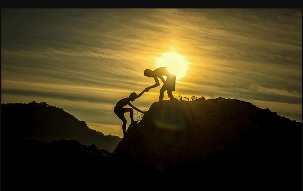 person helping another person climb up the mountain, sunset