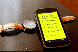 to do list on a smart phone and a wrist watch on a table