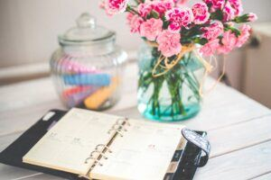 table, planner, vase, pink flowers, glass jar with candies