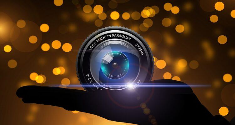 camera lenses, hand, gold light in the background